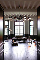 This room, painted in contrasting black and white, links Olivier's and Florence's studios and, while minimally furnished, is illuminated with a number of important lights, including a pendant light by Ron Gilad