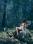 Beautiful sexy half nude woman in a light summer dress revealing her naked breast and legs sitting on rocks in a forest, bathing in sunshine with dreamy romantic expression