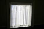 Net curtain in window of dark room letting in light