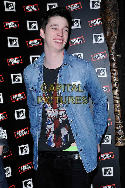 """ASH STYMEST .The """"Jersey Shore"""" launch party at Mahiki, London, England..February 8th, 2011.half length blue shirt denim side black trainers trousers union jack mtv logo t-shirt tee .CAP/CAN.©Can Nguyen/Capital Pictures."""