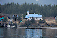 A boat travels past the Russian Orthodox Church in the Native village of Tatitlek, in Prince William Sound, Southcentral Alaska on a spring day in early May.