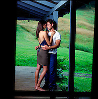 Couple standing on porch embracing<br />
