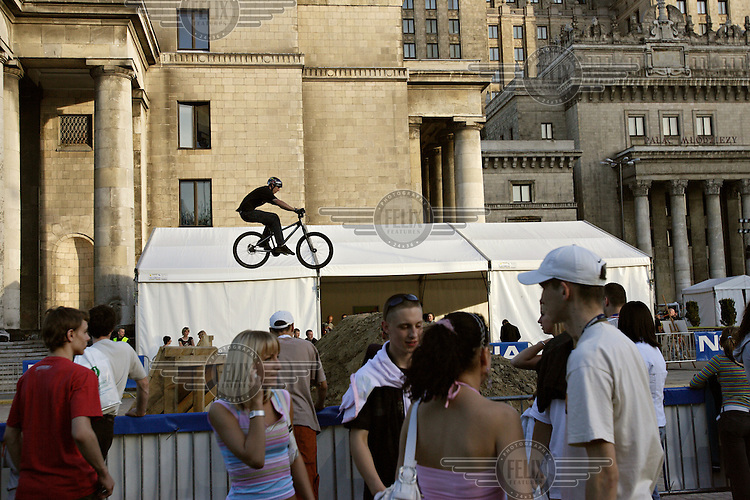 Teenagers watch as BMX bikers perform stunts at a sports and music event sponsored by mobile phone company Nokia, at the Soviet-built Palace of Culture.