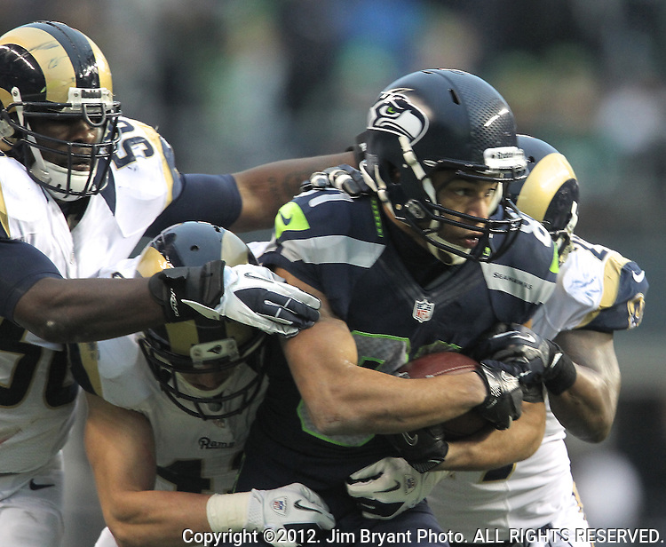 Seattle Seahawks Golden Tate is dragged down from behind by St. Louis Rams safety  Quintin Mikell, Craig Dahl, and linebacker Jo-Lonn DUnbar after catching an 18-yard pass from quarterback Russell Wilson at CenturyLink Field in Seattle, Washington on December 30, 2012.   Tate caught four passes for 105 yards in the Seahawks 20-13 come from behind win over the Rams.    © 2012. Jim Bryant Photo. All Rights Reserved.