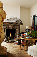 The atelier is dominated by a massive fireplace and furnished in Voorjans' eclectic signature style