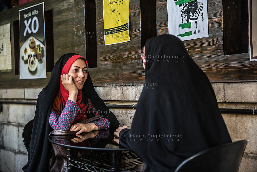 due ragazze velate sedute al bar <br />