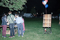 """People gather around a campaign table after entrepreneur and Democratic presidential candidate Andrew Yang spoke to a large crowd in Cambridge Common near Harvard Square in Cambridge, Massachusetts, on Mon., September 16, 2019. Yang's unlikely presidential bid is centered on his idea for a """"Freedom dividend,"""" which would give USD$1000 per month to every adult in the United States. After appearing in three Democratic party debates, Yang has risen in polls from longshot candidate to within the top 10."""