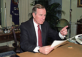 United States President George H.W. Bush poses for photographers after delivering an address to the nation from the Oval Office of the White House in Washington, DC on Christmas Day, December 25, 1991 announcing the resignation of President Mikhail Gorbachev as President of the Union of Soviet Socialist Republics, marking the collapse of the Soviet Union and the end of the Cold War.<br />