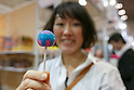 A woman shows an American lollipop candy during the 42nd International Food and Beverage Exhibition (FOODEX JAPAN 2017) in Makuhari Messe International Convention Complex on March 8, 2017, Chiba, Japan. About 3,282 companies from 77 nations are participating in the Asia's largest food and beverage trade show. This year organizers expect 77,000 visitors for the four-day event, which runs until March 10. (Photo by Rodrigo Reyes Marin/AFLO)