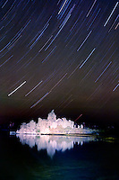 Star trails dazzle the night sky over the illuminated tufa at Mono Lake