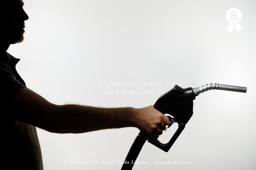 Silhouette of man holding fuel pump (Licence this image exclusively with Getty: http://www.gettyimages.com/detail/sb10068346bu-001 )