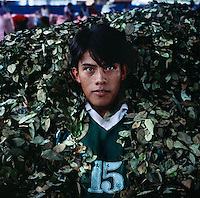 18-year-old Rodriguez Gomez sits in his pile of coca leaves before packing them into bags in order to sell later in the day in Eterazama, Bolivia. Every three months, the Gomez family harvests their coca plants to sell. While it is difficult to make a solid living growing coca, Gomez says he plans to continue working with the plant and hopes to take over the family farm when he grows up.