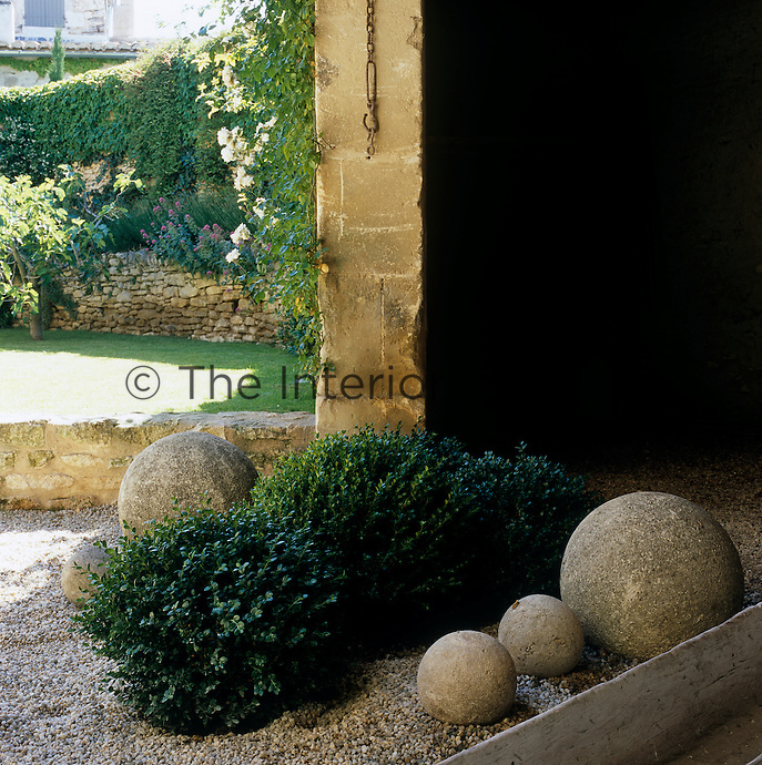 The gravel courtyard garden is decorated with box and stone balls of varying sizes