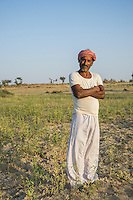 Guar farmer Bhanwarlal Sharma, 60, poses for a portrait in his agriculture field in Bamanwali village, Bikaner, Rajasthan, India on October 24th, 2016. Non-profit organisation Technoserve works with farmers in Bikaner, providing technical support and training, causing increased yield from implementation of good agricultural practices as well as a switch to using better grains better suited to the given climate. Photograph by Suzanne Lee for Technoserve
