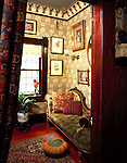 Portland, Oregon. c.1890. A small, eight by ten foot second bedroom off the dining room was made into an office.  Taking out the closet left just enough room for a Victorian recamier - button tufted of course. Serene swirls of chrysanthemums cover the walls; the hand-blocked, vegetable dyed Morris paper was bought on a trip to London.  Opaque, stained glass was added to screen out the neighboring house, and the homeowner even hand stenciled the window shade.