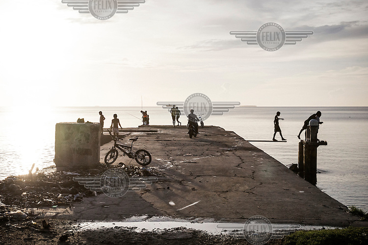 People fishing and playing on a jetty at sunset. <br /> Funafuti, a capital of Tuvalu, is located on the islet of Fongafale, part of Funafuti Atoll. It has a population over 6,000 people, making it the most populated atoll with 58% of Tuvalu's population. Tuvalu has a population just over 10,000 people, most of whom live in the country's capital Funafuti. Increasing urbanisation, along with climate change, pose big threats to this tiny Pacific country. Migration from the outer islands to the main island of Fongafale is placing increasing pressure on water supplies and land availability, while employment opportunities in the small formal sector are limited. Moreover, stronger 'King Tides', Saltwater intrusion into the groundwater and extreme weather events are making this island nation one of the most vulnerable countries in the world.