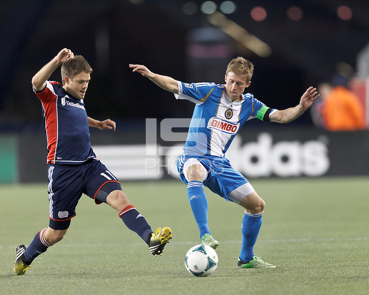 Philadelphia Union midfielder Brian Carroll (7) attempts to control the ball as New England Revolution defender Kelyn Rowe (11) closes..  In a Major League Soccer (MLS) match, the New England Revolution (blue/red) defeated Philadelphia Union (blue/white), 2-0 at Gillette Stadium on April 27, 2013.