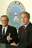 United States President George W. Bush (R) speaks next to US Secretary of Defense Donald Rumsfeld during a visit at the Pentagon March 25, 2003 in Arlington, Virginia. Bush asked Congress for a wartime supplemental appropriations of $74.7 billion to fund needs directly arising from the war in Iraq and the global war against terror.  <br /> Credit: Alex Wong / Pool via CNP