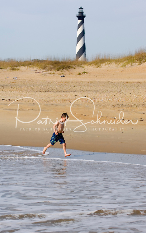 A young boy plays on the beach near the stately Cape Hatteras Lighthouse in North Carolina Outer Banks. ..Have model release.