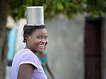 A woman carries a pot on her head as she walks in Batey Bombita, a community in the southwest of the Dominican Republic whose population is composed of Haitian immigrants and their descendents.