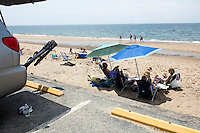 """Janice (from right, under umbrellas), Reid (13), Tristan (13), and Scott Marble and their dog Daisy, sit near their car at Herring Cove Beach in the Cape Cod National Seashore outside of Provincetown, Mass., USA, on Fri., July 1, 2016. At right, pieces of eroded asphalt lay in the sand. Portions of the parking lot have been closed after land eroded during storms earlier this year. The Marble family spend their summers in Orleans, Mass., located on Cape Cod, and spend the rest of their year in Medfield, Mass. Scott, age 60, says he's been coming to the beach at least 40 years, and the couple have taken the boys to the beach since they were babies. """"We miss the whole length of it,"""" Janice said when asked about how the destroyed road and parking lot have changed the beach."""