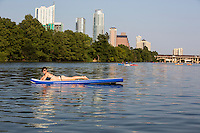 Young woman in bikini during stand up paddling on the crystal blue waters of Lady Bird Town Lake Austin. Austin, Texas.