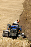 Farmer ploughing recently harvested field of crops