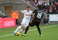 Barclays Premier League, Swansea City (White) V Norwich City (black) Liberty Stadium, Swansea, 08/12/12<br /> Pictured: Swansea's Angel Rangel runs at  Javier Garrido<br /> Picture by: Ben Wyeth / Athena <br /> Athena Picture Agency<br /> info@athena-pictures.com
