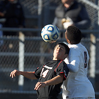 Northeastern University midfielder Dante Marini (14) and University of Connecticut midfielder George Fochive (9) battle for head ball. .NCAA Tournament. University of Connecticut (white) defeated Northeastern University (black), 1-0, at Morrone Stadium at University of Connecticut on November 18, 2012.
