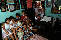The Ozil family pose in their tiny 16m sq home, there are 7 children, plus the parents, mother, Lourdes and father Jessy, 33. The live in the slum area of Manila called San Anreas Bukid (neighbour-hood) where families commonly have between 6- 12 children. There is no family planning available from the Government due to a law passed by the Mayor and they are too poor to pay for their own contraception.
