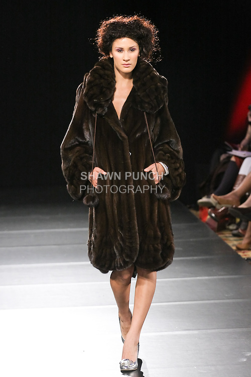 Model walks runway in a Kostas Fall 2011 collection fur coat, by Kostas Gagasoules, during Couture Fashion Week Fall 2011 in New York.
