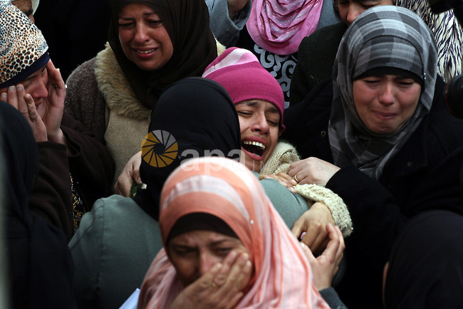 A sister of Jawaher Abu Rahmah is supported by other mourners during the funeral of Jawaher Abu Rahmah at the West Bank Village of Bil'in, on 01 January 2011. Jawaher, 36, who was protesting against Israel's West Bank separation barrier, was evacuated to the Ramallah hospital on 31 December 2010 after inhaling massive amounts of tear-gas during the weekly Friday protest in Bilin, and died on 01 January 2011 morning after she did not respond to medical treatment. Abu Rahmah was the sister of Bassem Abu Rahmah, who was killed during a protest in the same village, which is located about four kilometres from the Israel-West Bank border on 17 April 2009. Photo by Issam Rimawi