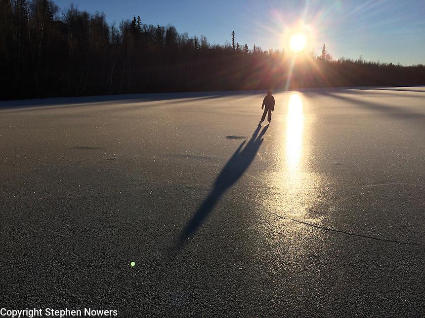 An ice skater on a lake near Palmer in Alaska's Matanuska Valley.
