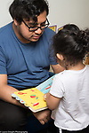 Education Preschool 2-3 year olds girl and father looking at book at start of day