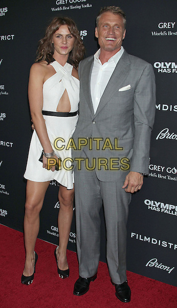 "Jenny Sanderson & Dolph Lundgren.""Olympus Has Fallen"" Los Angeles Premiere held at ArcLight Cinemas Cinerama Dome, Hollywood, California, USA..March 18th, 2013.full length white dress grey gray suit shirt criss cross black belt clutch bag couple .CAP/ADM/RE.©Russ Elliot/AdMedia/Capital Pictures."