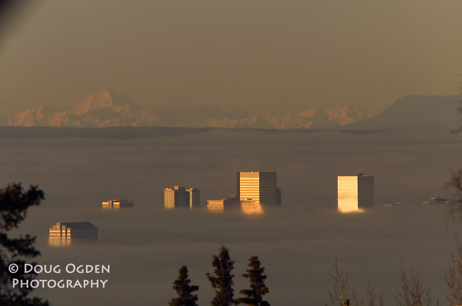 Fog laying around buidlings with Mount McKinley in background, Anchorage, Alaska