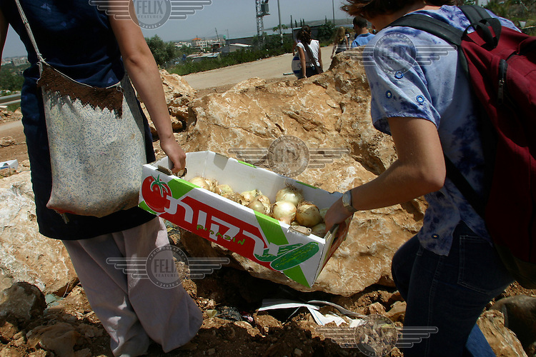 Just in case, two peace activists carry onions to be used in case of tear gas attack by Israeli soldier, during a demonstration through the Palestinian village of Mas'ha