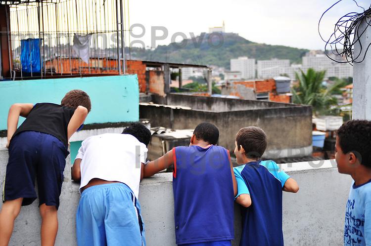 Meninos no terraço olhando a favela.  Conjunto de favelas do Alemão, Rio de Janeiro, Brasil.