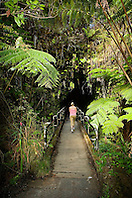 Woman visitor walking into Thurston Lava Tube ( Nahuku ), Hawaii Volcanoes National Park, Kilauea, Big Island, Hawaii