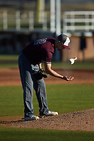 Concord Mountain Lions relief pitcher Anthony Stehlin (12) uses the rosin bag during the game against the Wingate Bulldogs at Ron Christopher Stadium on February 2, 2020 in Wingate, North Carolina. The Mountain Lions defeated the Bulldogs 12-11. (Brian Westerholt/Four Seam Images)