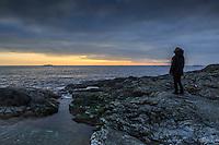 Människa ensam på en klippa vid havet med horisonten på Torö i Stockholms skärgård.