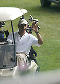 Martha's Vineyard, MA - August 25, 2009 -- United States President Barack Obama waves to photographers as he drives a golf cart during a round of golf at Mink Meadows GC, Vineyard Heaven, Massachusetts on Tuesday, August 25, 2009..Credit: Michael J. Maloney - Pool via CNP