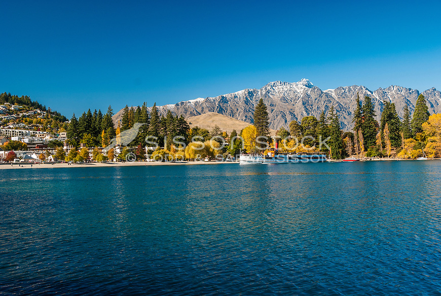 The TSS Earnslaw steams past Queenstown Gardens and the Remarkables Mountains on Lake Wakatipu,  Central Otago, South Island, New Zealand.