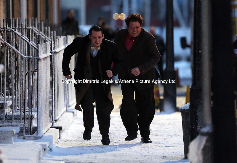 Pictured L-R: Elijah Wood with Celyn Jones running while rehearsing a scene. Tuesday 11 February 2014<br /> Re: A Swansea street was transformed into 1950s New York for new Dylan Thomas biopic 'Set Fire to the Stars' starring Holywood actor Elijah Wood.<br /> Gloucester Place in Swansea Marina was used to film a snowy scene in New York.<br /> Half a dozen 50s American cars were used for the scene played by Elijah Wood and Celyn Jones.<br /> The new movie will explore the fractious relationship between Dylan Thomas played by Jones and John Malcolm Brinnin played by WOod, who brought the Welshman to the USA and acted as his tour agent.