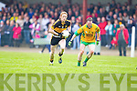 Gneeveguilla's Mike B Murphy falls injured as Colm Cooper of Dr Crokes breaks away in Gneeveguilla last Sunday evening in round 1 of the Garvey's Supervalue County Senior Championship.