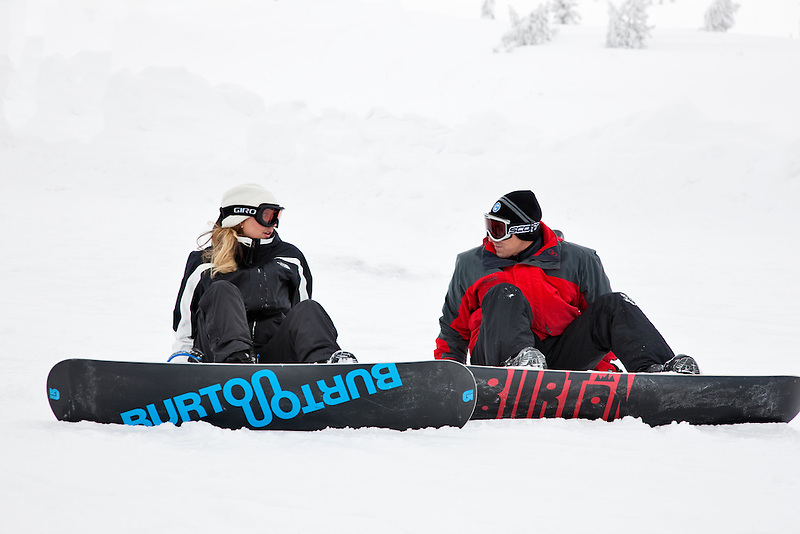 Couple talking while resting from snowboarding, Oregon