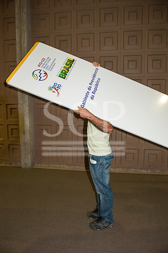 "A man carries a panel marked ""Cabinet of the Presidency of Brazil"" during the build-up at the Rio Centre. United Nations Conference on Sustainable Development (Rio+20), Rio de Janeiro, Brazil. Photo © Sue Cunningham."