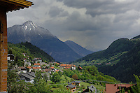Alpine village with mountains in the background on a grey day. Wenns, Imst district, Yyrol,Tirol, Austria.