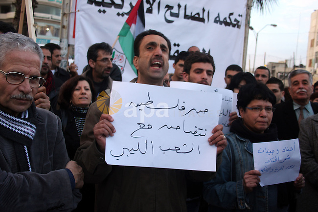 Palestinians hold up placards during a protest against Libyan leader Moamer Kadhafi,in the West Bank city of Ramallah on Feb. 22, 2011. Photo by Issam Rimawi