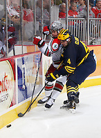 OSU Max MCCormick goes up against Michigan's Kevin Clare in the second period at Value City Arena in Columbus Dec. 2, 2013.